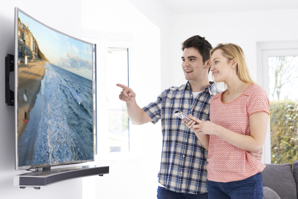 Young Couple With New Curved Screen Television At Home